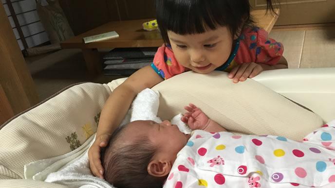 生まれた赤ちゃんをなでなでする優しいお姉ちゃん