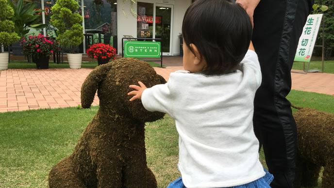 犬の形の置物にたっちする動物好きの赤ちゃん