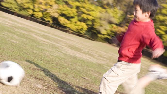公園で大好きなサッカーをして遊ぶ男の子