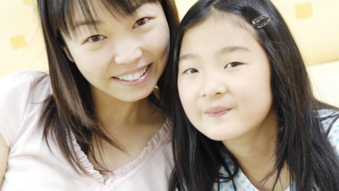 ママとツーショット写真を撮る女児