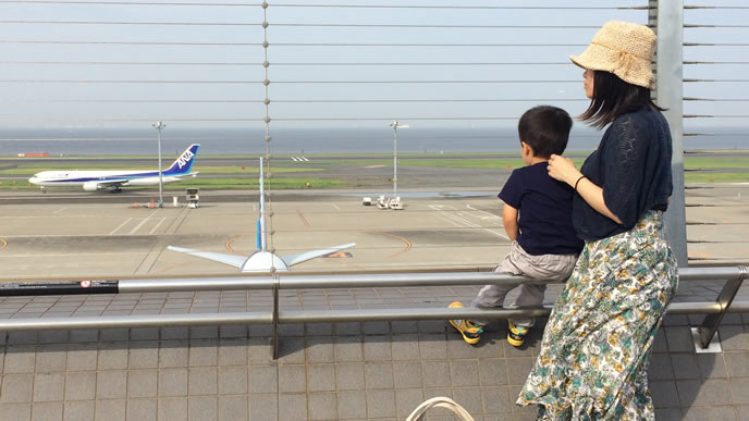 ママと一緒に飛行機を見学する男の子