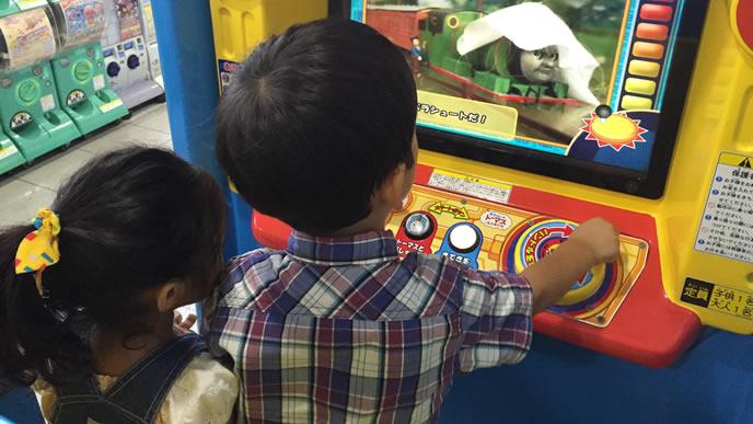 ゲームセンターで妹と一緒に遊ぶ兄