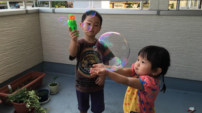 シャボン玉で遊ぶ兄と兄の作ったしゃぼん玉を手に持つ妹