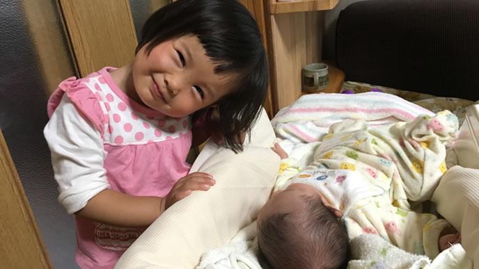 新生児の弟と一緒に写真を撮る姉
