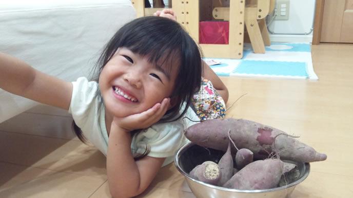幼稚園の芋ほりで取ってきた芋を自慢する女の子