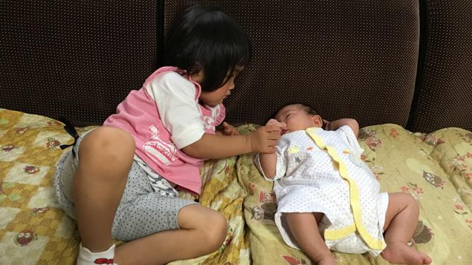 妹の手を握り寝かしつける姉