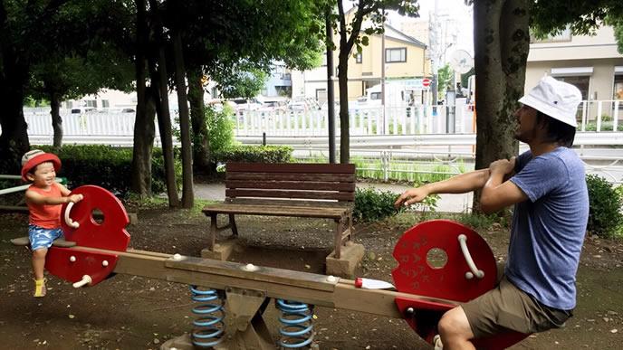 パパと楽しく公園のシーソーをする男の子