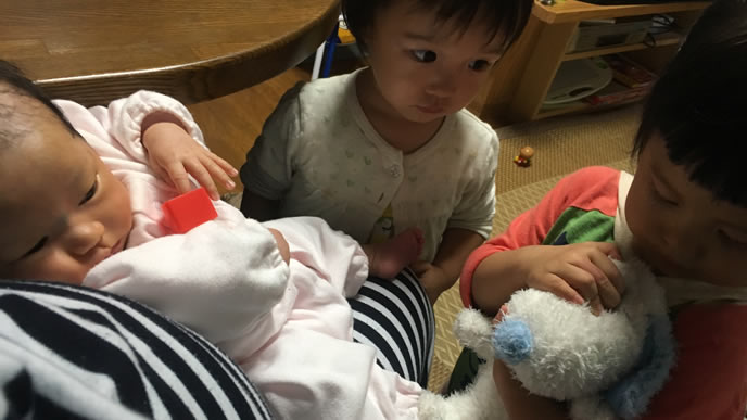 新生児の赤ちゃんのお世話をする女の子