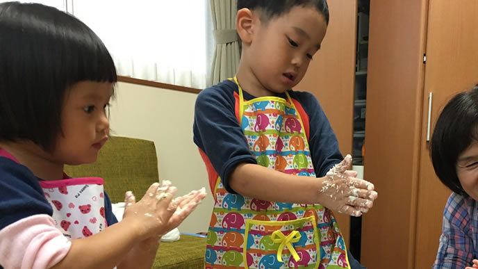 粉をこねて作る料理中の兄と妹