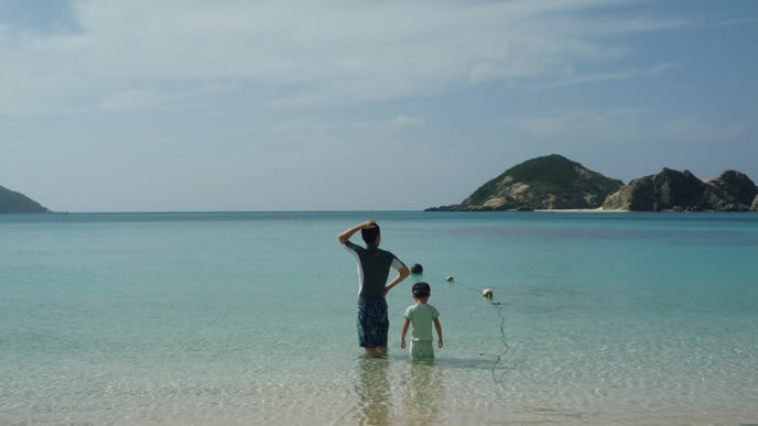 パパと一緒に海で泳ごうとする男の子