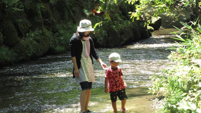 楽しそうに川でママと遊ぶ男の子