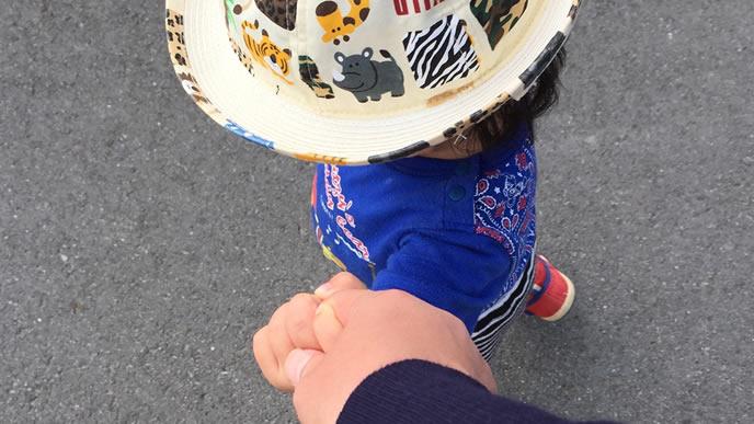 お気に入りの帽子をかぶりパパとお散歩中の幼稚園児