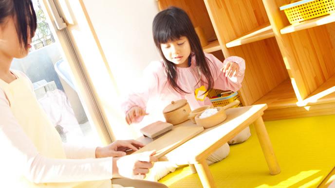 ママが迎えにくるまで保育園の先生と遊ぶ女の子