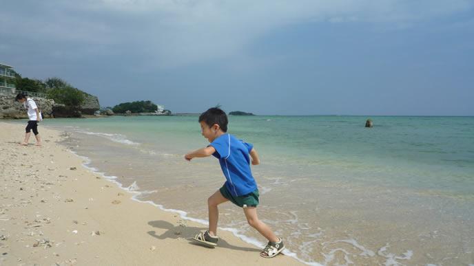 中間反抗期でも浜辺で走り回る元気な男の子