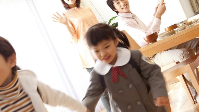 小学校と幼稚園に向かう子供達を見送るママとパパ