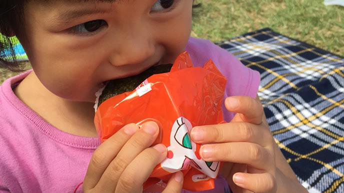 可愛い包みに入ったおにぎりを食べる女の子