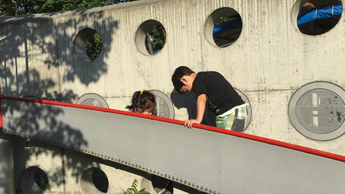 公園の滑り台で楽しそうに遊ぶ兄妹
