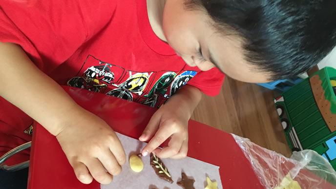 クッキーで遊んでいる男の子