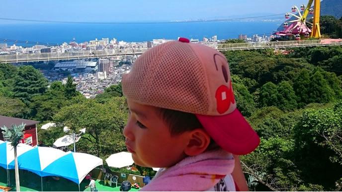 高台にある遊園地に家族旅行中の男の子