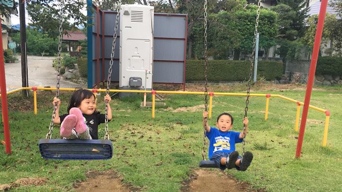 公園のブランコで遊ぶ兄妹