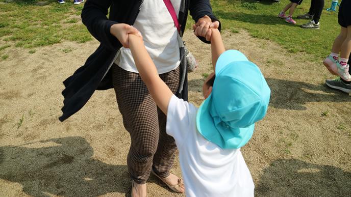 幼稚園の行事で子供とダンスを踊るママ
