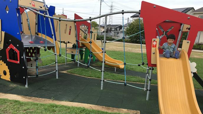 公園の遊具で一人滑り台を楽しむ2歳児