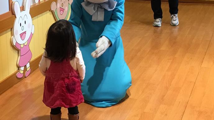 青いキャラクターを不思議そうに見つめる女の子