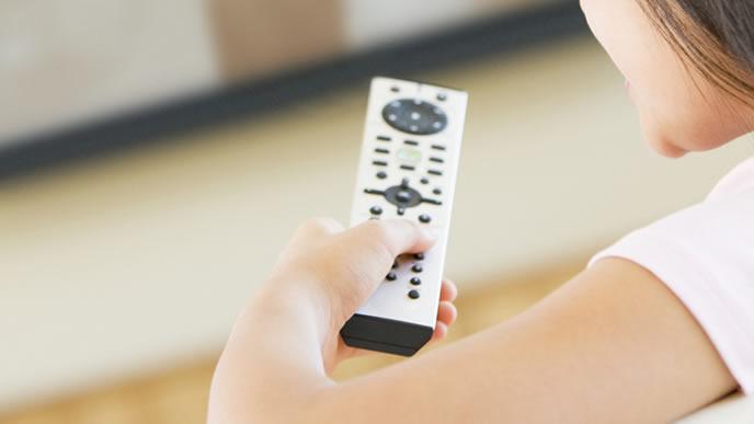 家でテレビを楽しむ女性