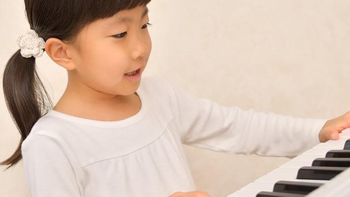 ピアノのお稽古をしている幼稚園の子供