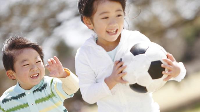サッカーボールを抱えて走る男の子