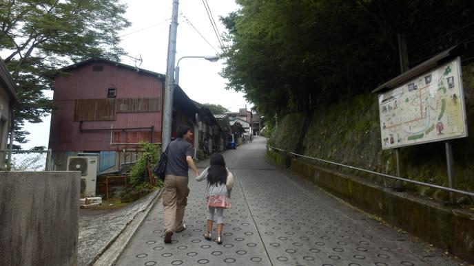 パパと手を繋いで坂を上る女の子
