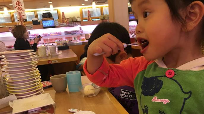 回転寿司のお店でごはんを食べる女の子