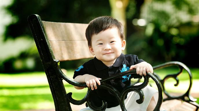 公園のベンチに座る笑顔の男の子