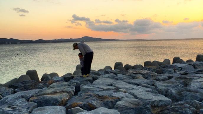 海岸の岩場でパパと遊ぶ子供