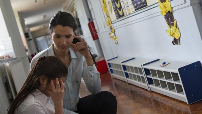 頭を抱える教え子を心配そうに見つめる教師