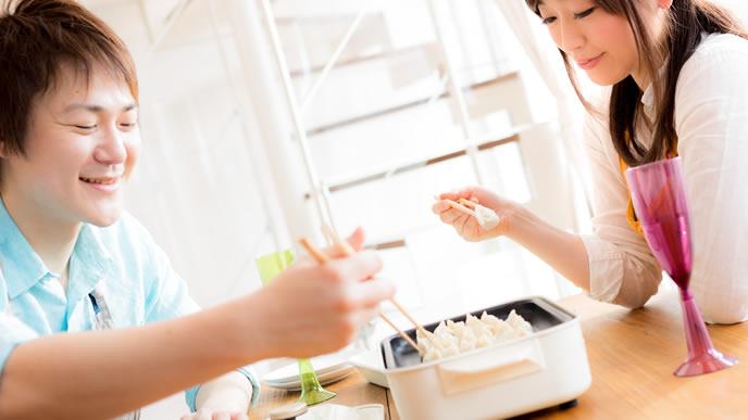 仲よく餃子を食べる家庭円満な夫婦
