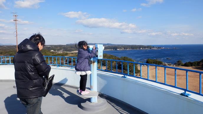 望遠鏡で遠くの景色を見る女の子