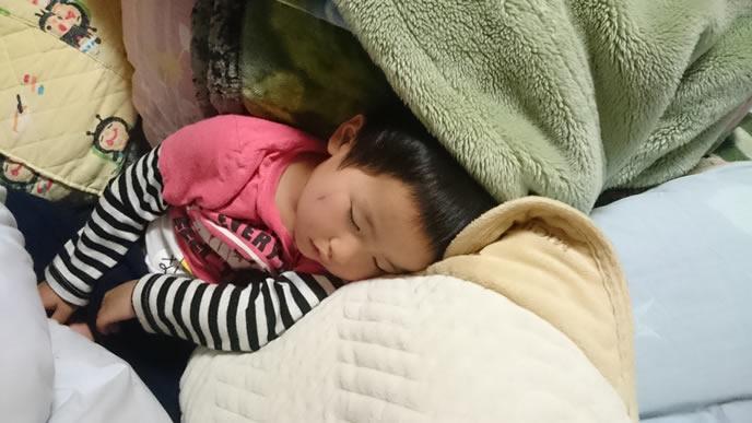 毛布の中で寝ている子供