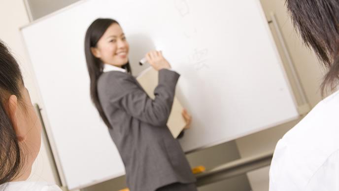 小学生の生徒に勉強を教える塾の先生