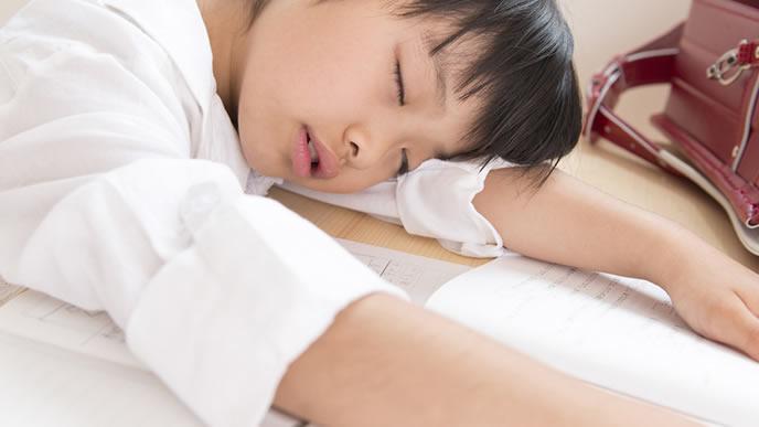 疲れて学校の机で寝る小学生
