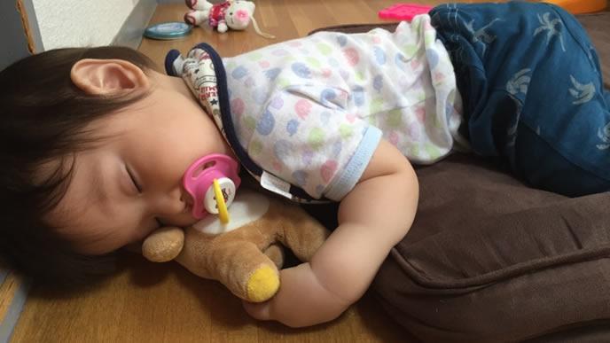 クマのぬいぐるみを枕にする赤ちゃん