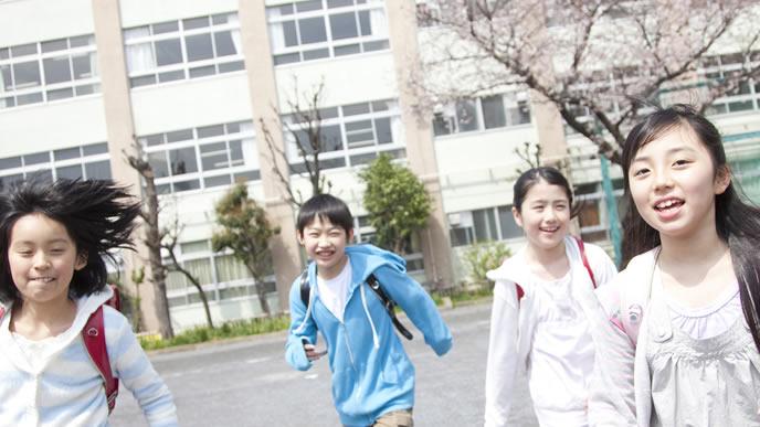 校庭で元気に走り回る小学生