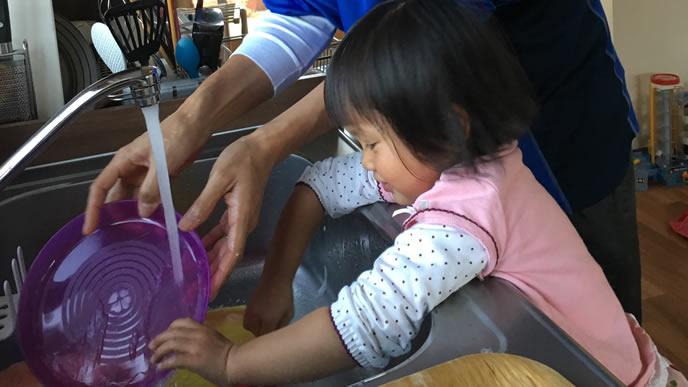 皿洗いのお手伝いをする女の子