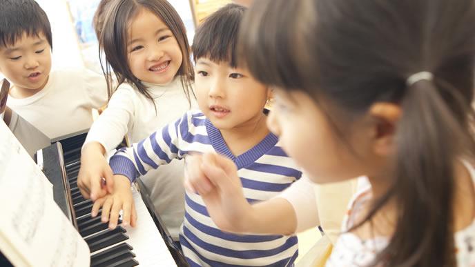 お迎えまで先生にピアノを教えてもらう園児