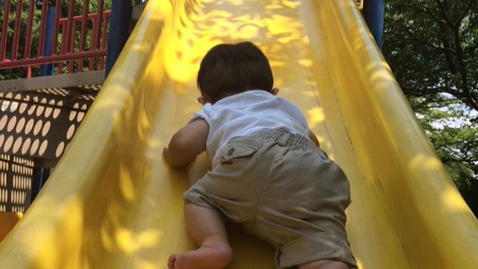 逆から滑り台を登る男の子