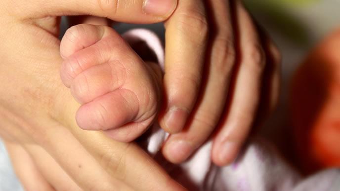 生まれてきた赤ちゃんの手を握るママ