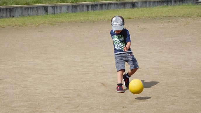 一人でサッカーをする少年