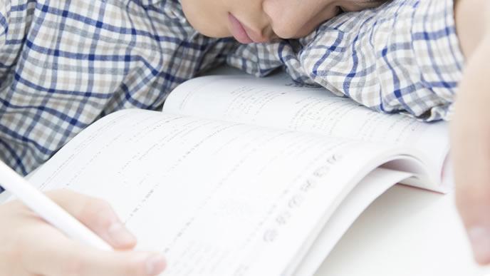勉強中に居眠りする中学生