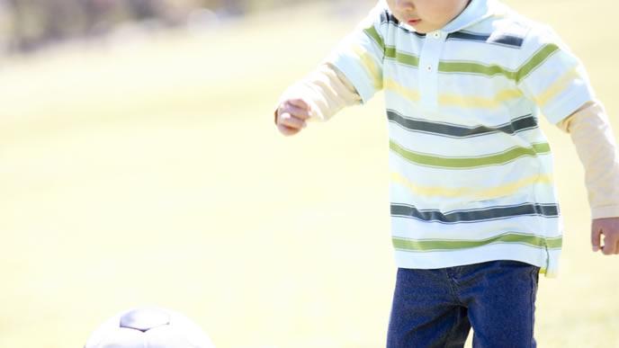 公園でサッカーを楽しむ男の子