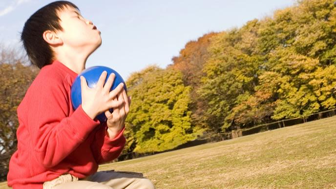 学校終わりにボールで遊ぶ男の子